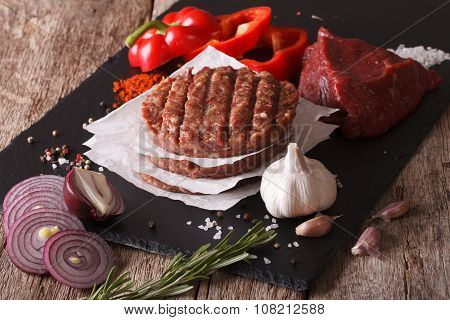 Raw burgers cutlets close-up with the ingredients on the table. horizontal poster