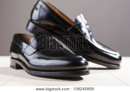 Footwear Concepts. Pair Of Stylish Fashionable Real Leather Black Penny Loafers. Placed Against Gray