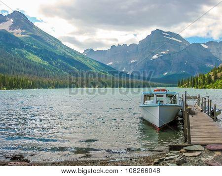 Fishing boat docked at the wooden jetty at Lake McDonald, Glacier National Park, Montana, United States. poster