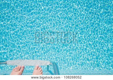 Feet About To Climb Down Ladder Into A Sparkling Pool