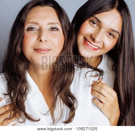 cute pretty teen daughter with mature mother hugging, fashion style brunette makeup close up