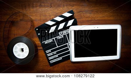 Screenwriter desktop with movie clapper board film reel and notepad poster