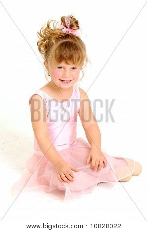 Little girl wearing pink ballet outfit and sit on floor