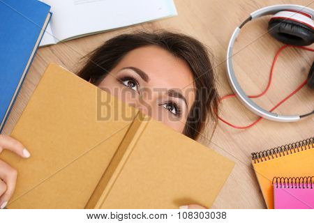 Beautiful Woman Lying On Floor Covering Face With Book Dreaming