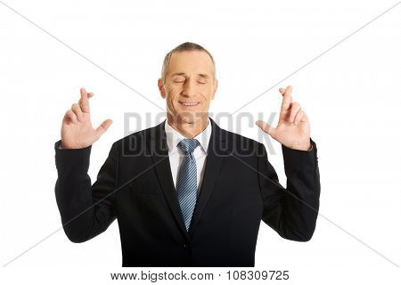 Mature businessman making a wish with fingers crossed.