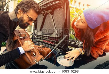 Beautiful Fashion Couple Going To Vacations, Loading Their Car Boot With Leather Travel Suitcases  -