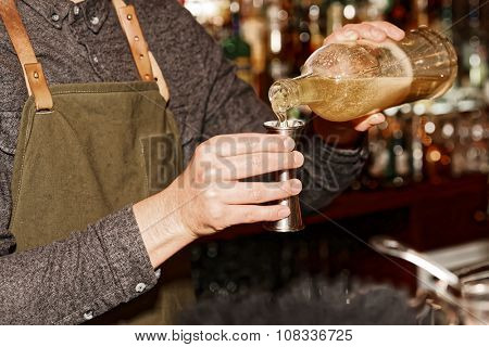 Old styled bartender is pouring liquor in metal jigger