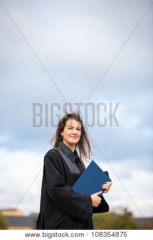Pretty, young woman celebrating joyfully her graduation - spreading wide her arms, holding her diploma, savouring her success (color toned image; shallow DOF)