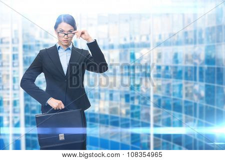 Portrait of businesswoman keeping case, blue background. Concept of leadership and success