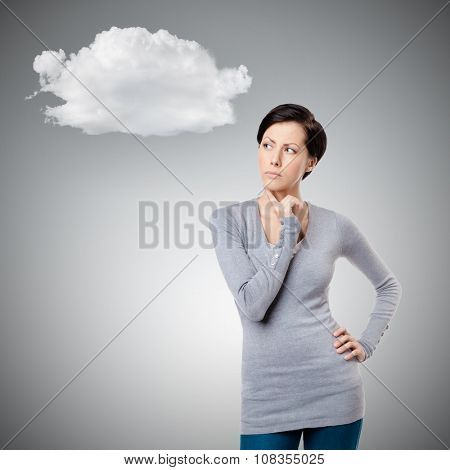Pensive young lady touches her neck, isolated on grey background