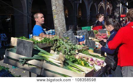 Market trader selling vegetables at Revel France.