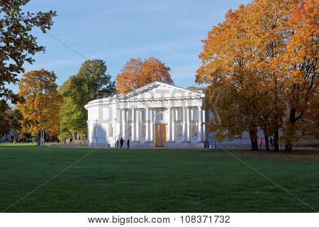 ST. PETERSBURG, RUSSIA - OCTOBER 16, 2015: People walking in front of kitchen building of Yelagin Palace in an autumn day. The building erected in 1818-1822 by design of Carlo Rossi