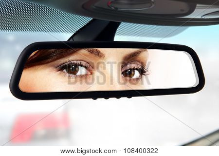 woman sits on driver's seat and Looks in the rear-view mirror