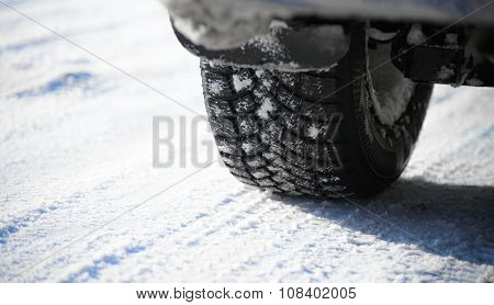 Close-up Image of Winter Car Tire on the Snowy Road. Drive Safe Concept