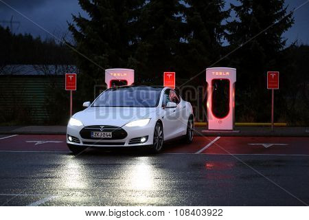 Tesla Model S Arrives At Supercharger Station At Night