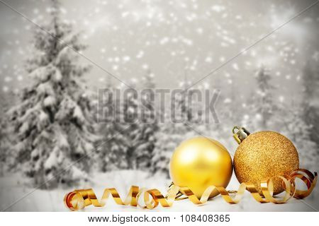 Golden Christmas decorations in the snow, snow cowered pine trees in the background