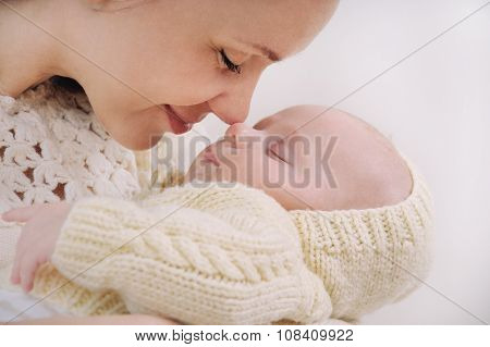 Close Up Mother's Face Touching Nose By Nose Of Her Baby
