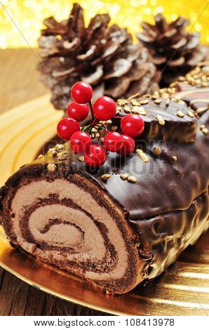 a yule log cake, traditional of christmas time, in a golden tray with some natural ornaments, such as pinecones