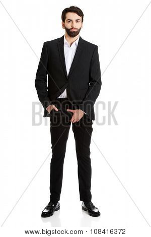 Young businessman holding his crotch because of pain.