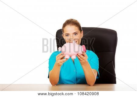 Young female doctor or nurse holding piggybank.