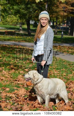 Girl And Dog Standing In Autumn Leaves