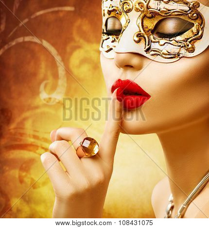 Beauty model woman wearing venetian masquerade carnival mask at party over holiday golden background. Christmas and New Year celebration. Glamour lady with perfect make up and accessories