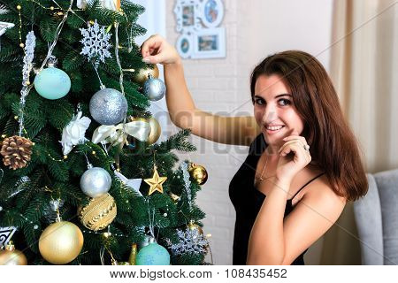 Beautiful Girl In A Black Dress Decorates Christmas Tree