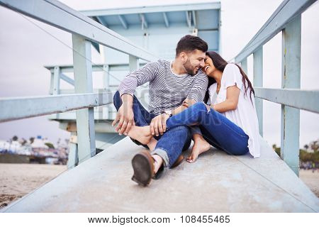 loving romantic Hispanic couple snuggling with each other near santa monica shot with selective focus poster