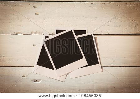 Instant photos on wooden floor with copy space