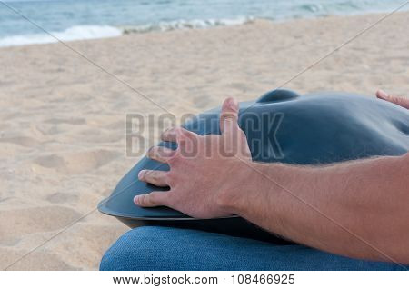 Busker sit on sand and play the Hang or handpan with sea On background. The hang is a traditional et