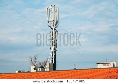 GSM transmitters on a red building roof in city center