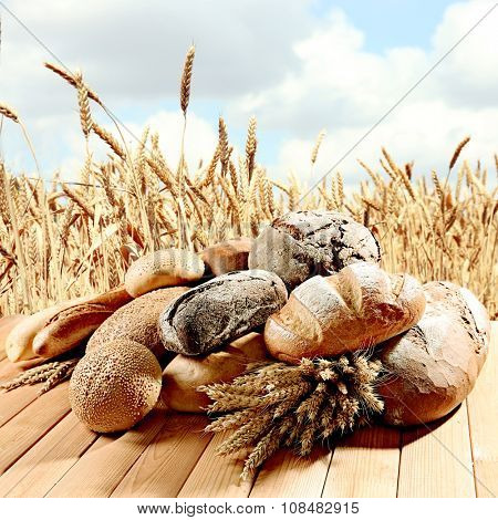Fresh bread on wheatfield background