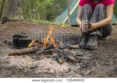 Girl Sitting While Camping Near The Fire Heated And Drink Hot Tea