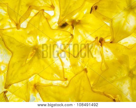 back lit yellow ripe slices of star fruit carambola