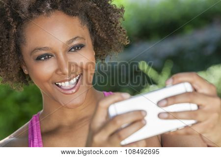 African American mixed race young woman or girl taking selfie photograph using smartphone or cell phone