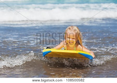 Little Child Swimming With Bodyboard On The Sea Waves