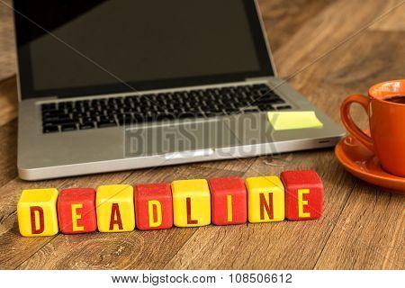 Deadline written on a wooden cube in a office desk