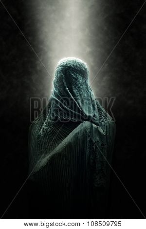 Veiled Islamic woman wearing a burka standing in a beam of overhead light in atmospheric darkness in a spiritual portrait