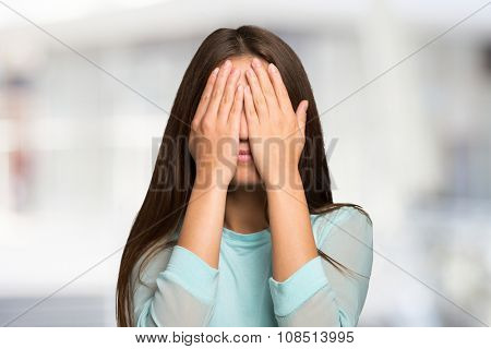 Woman covering her face and eyes