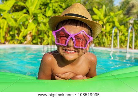 Boy in star-shaped sunglasses on green airbed in the swimming pool outside in summer