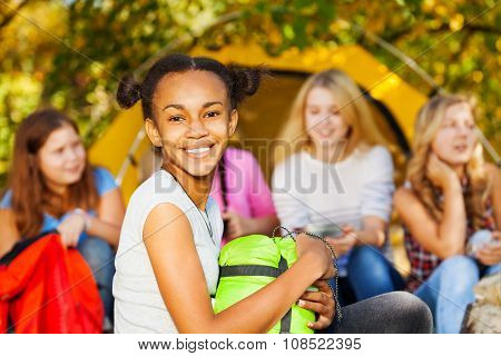 African happy girl holding green sleeping bag