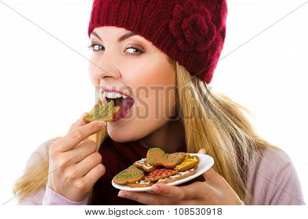 Happy Woman In Woolen Cap And Shawl Eating Gingerbread Cookies, White Background, Christmas Time