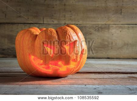 bright light in pumpkins on wood background.