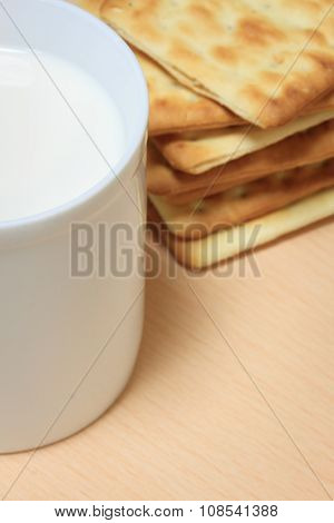 Selective focus milk and blur craker on wood background.