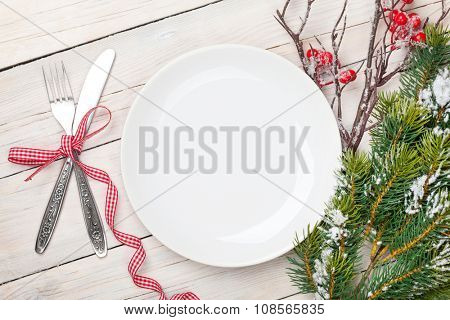 Empty plate, silverware and christmas tree. View from above over white wooden table background