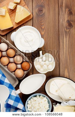 Dairy products on wooden table. Sour cream, milk, cheese, eggs, yogurt and butter. Top view with copy space