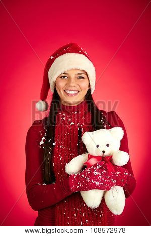 Pretty girl in Santa cap holding white teddybear