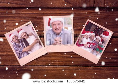 Instant photos on wooden floor against festive couple hugging on the couch