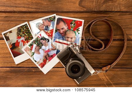 Senior man giving a kiss and a Christmas present to his wife against instant photos on wooden floor