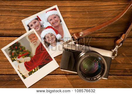 Smiling santa claus writing list against instant photos on wooden floor